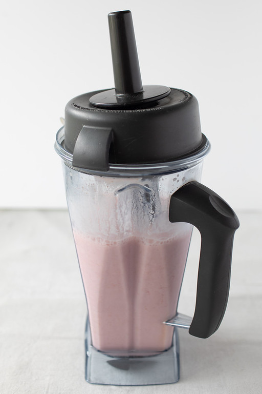 Vitamix blender with raspberry smoothie blended up.