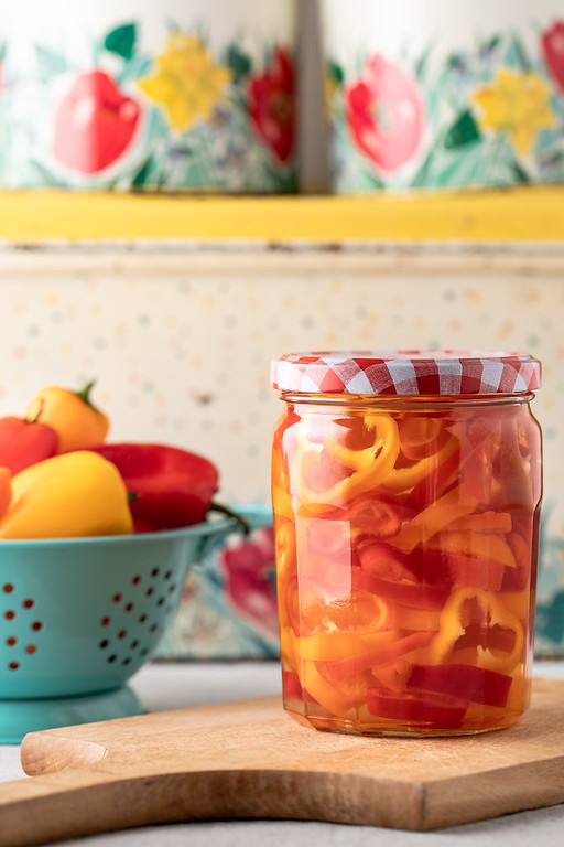 Jar filled with pickled peppers in front of a blue bowl filled with peppers.