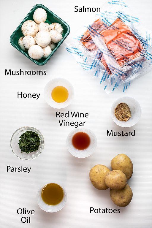 Ingredients to make a one pan salmon dinner with potatoes and mushrooms.