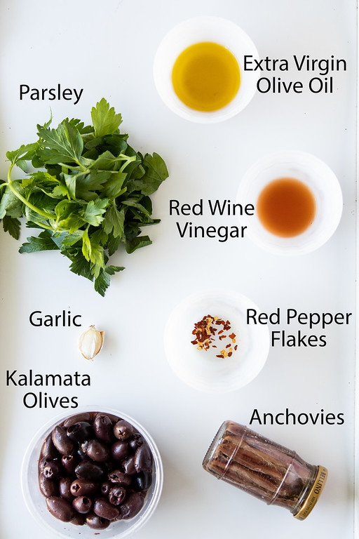 Ingredients for making a black olive tapenade: olive oil, red wine vinegar, red pepper flakes, parsley, garlic, kalamata olives and anchovies.