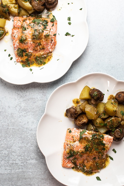 Two plates of roasted salmon with potatoes and mushrooms with a vinaigrette drizzled on top.