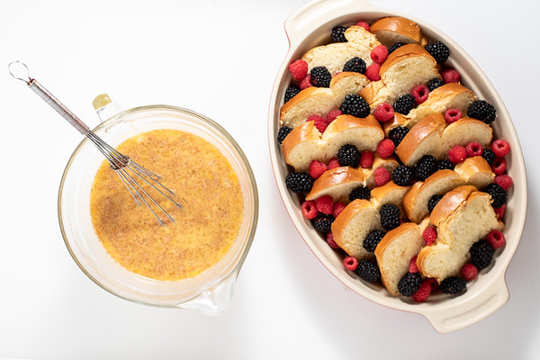 Bowl of whipped eggs and casserole of bread and berries.