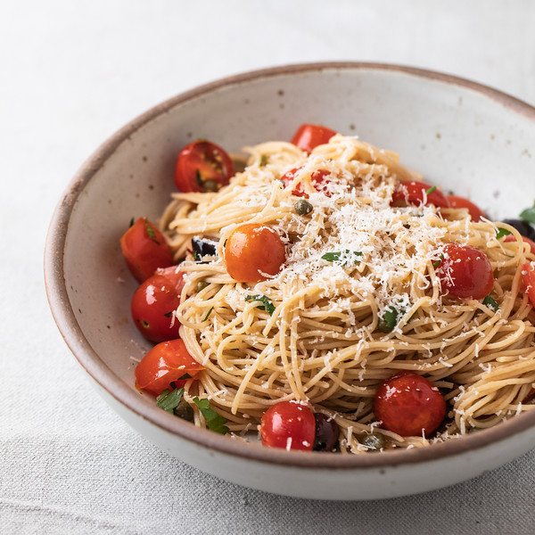 Bowl of pasta puttanesca topped with Parmesan cheese.