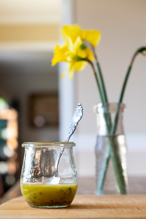 Jar of homemade greek vinaigrette with a vase of daffodils in the background.