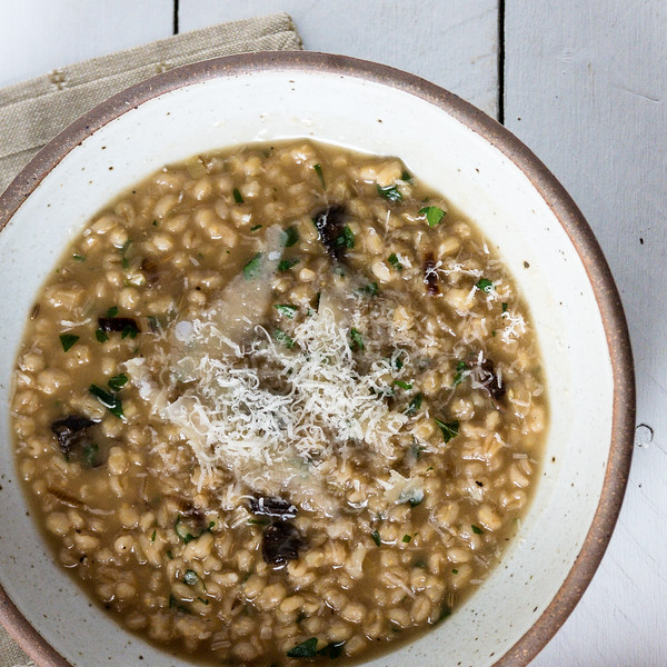 Cream colored bowl on a white background with a brown risotto topped with grated cheese.