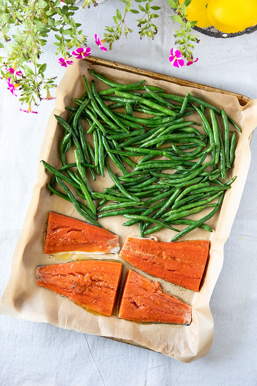 Tray lined with parchment paper wit salmon and green beans.
