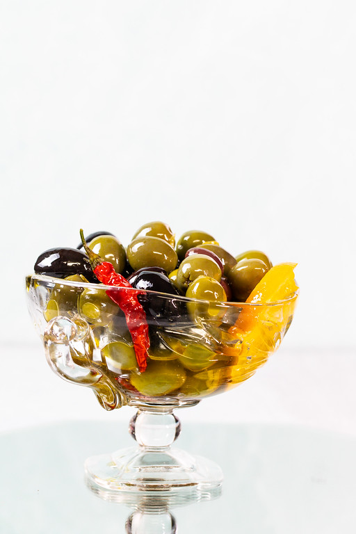 Glass bowl filled with marinated olives.
