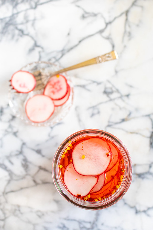 Overhead shot of a jar of pickled radishes on a marble background