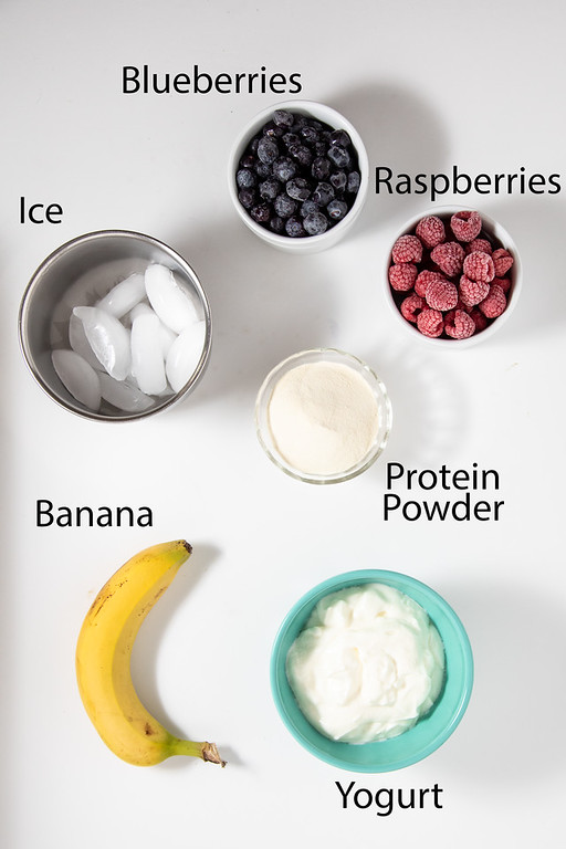 Photo showing ingredients: blueberries, ice, raspberries, protein powder, yogurt and a banana.