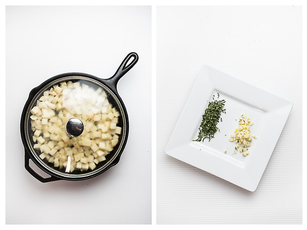 Potatoes in skillet with a lid and a plate with garlic and rosemary.