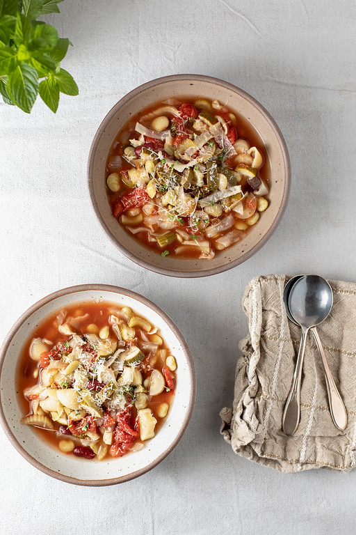 Two bowls of minestrone soup.