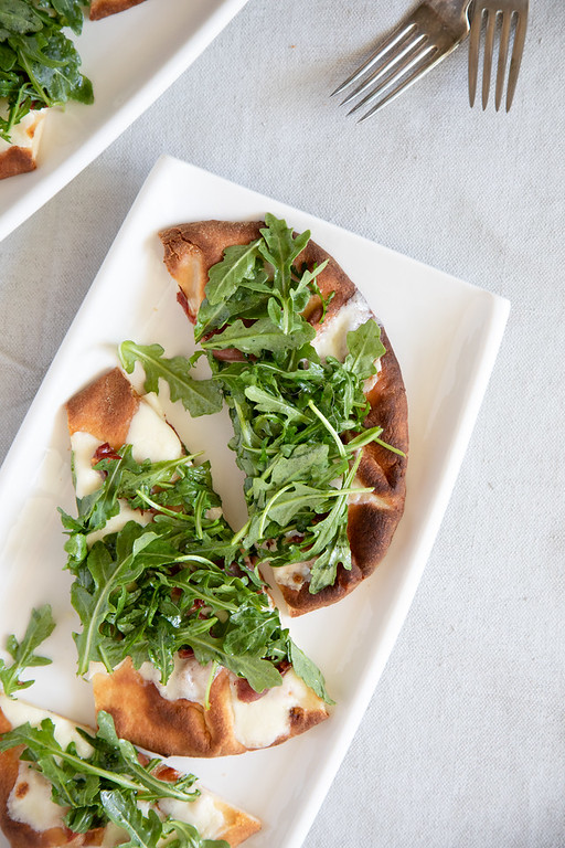 Prosciutto pizza with arugula on a white plate.