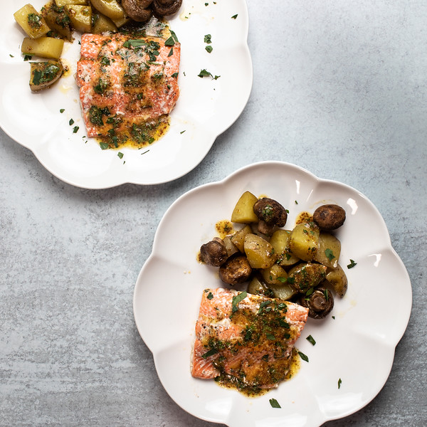 Two plates with salmon, potatoes and mushrooms.