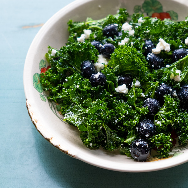 Close up photo of kale salad with blueberries and feta cheese.