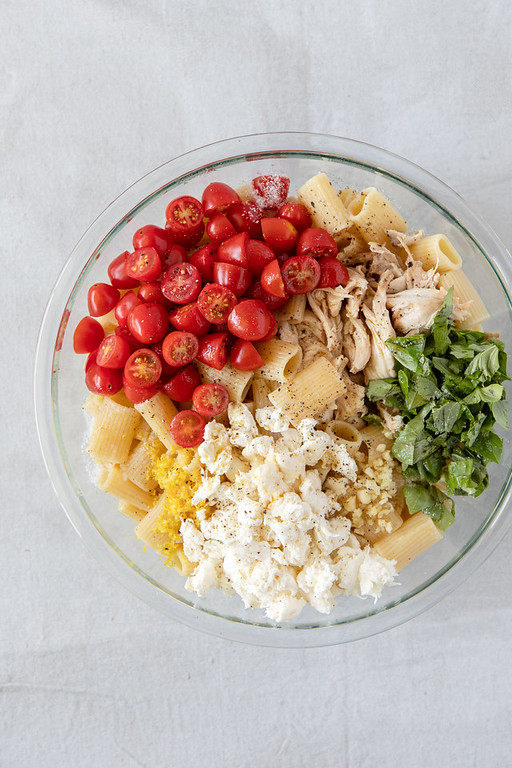 Bowl with tomatoes, chicken, basil, garlic, cheese and lemon zest on top of pasta.