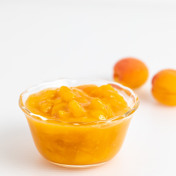 Small bowl of bright orange apricot fruit compote.