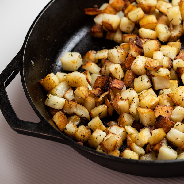 Crispy browned potato cubes in a cast iron skillet.