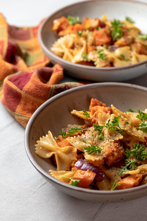Two bowls of pasta with sweet potatoes and sprinkled with parsley.