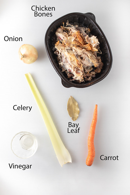 Ingredients to make homemade chicken stock: chicken bones, onion, celery, carrot, bay leaf and vinegar.