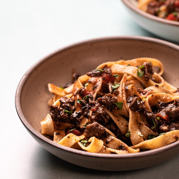 Bowl of pasta topped with a meaty mushroom ragu.