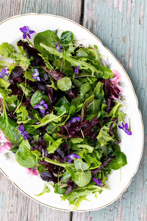 Platter filled with an herb salad and violet flowers.