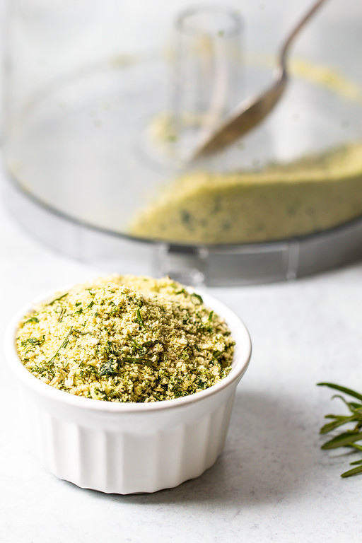 Bowl of herbed bread crumbs with a food processor in the background.