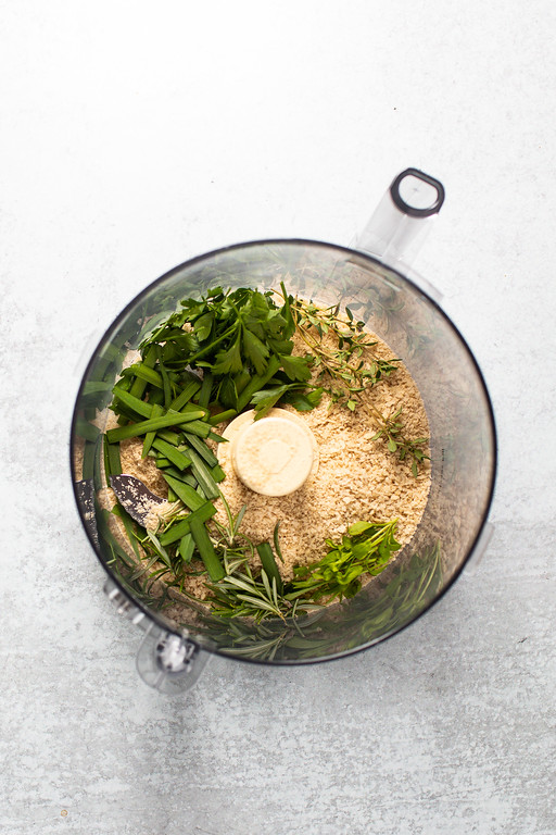 Food processor bowl with bread crumbs and fresh herbs.