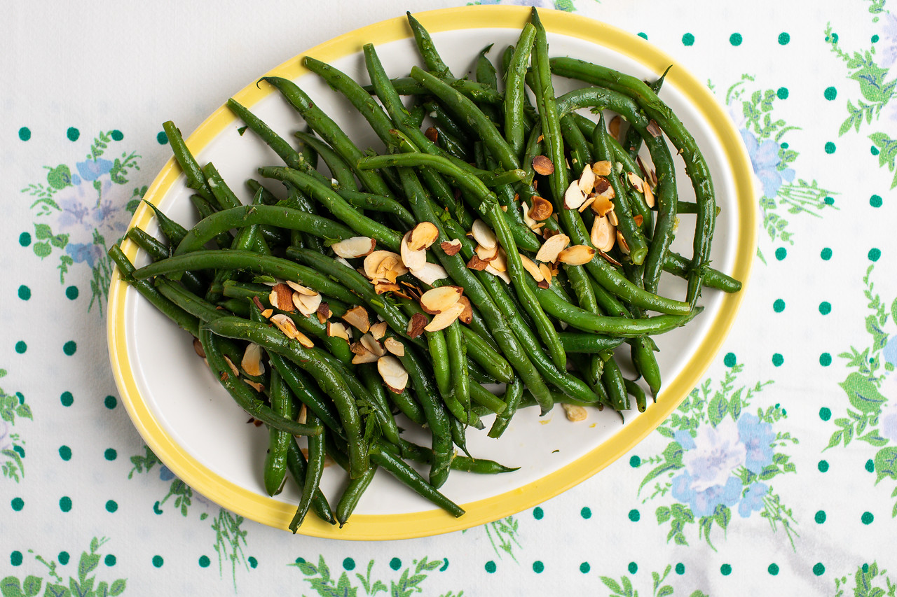 Platter of green beans on a vintage tablecloth.