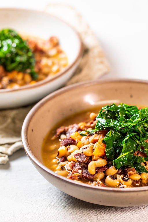 Bowl of black eyed peas topped with bright green collard greens.