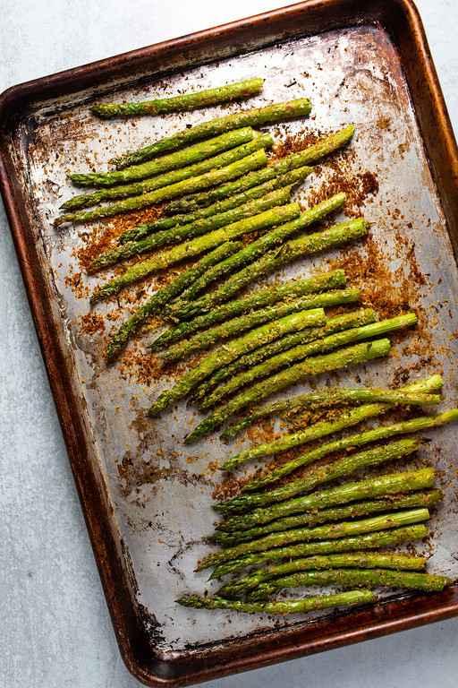 Baking sheet with roasted asparagus with bread crumbs and parmesan cheese on them.