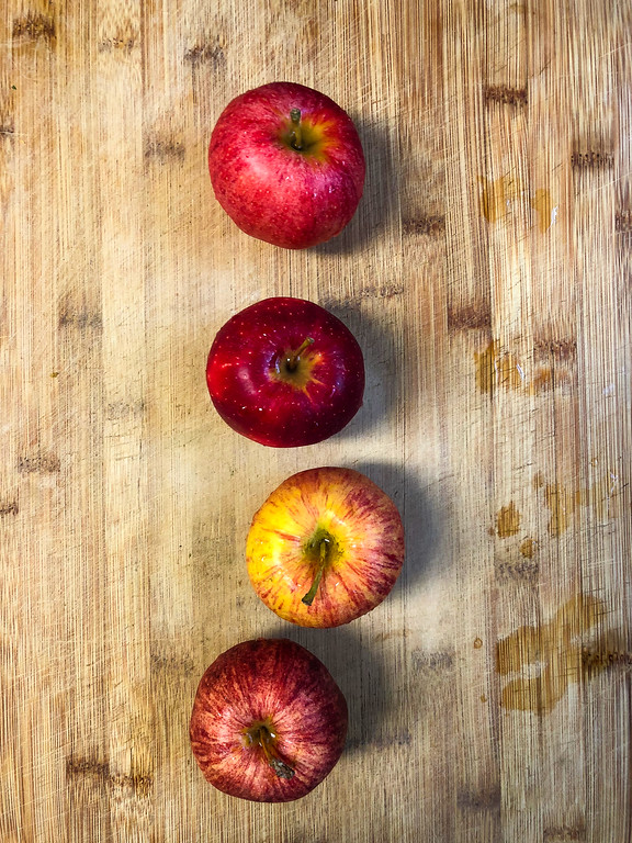 Four apples on a wooden cutting board.