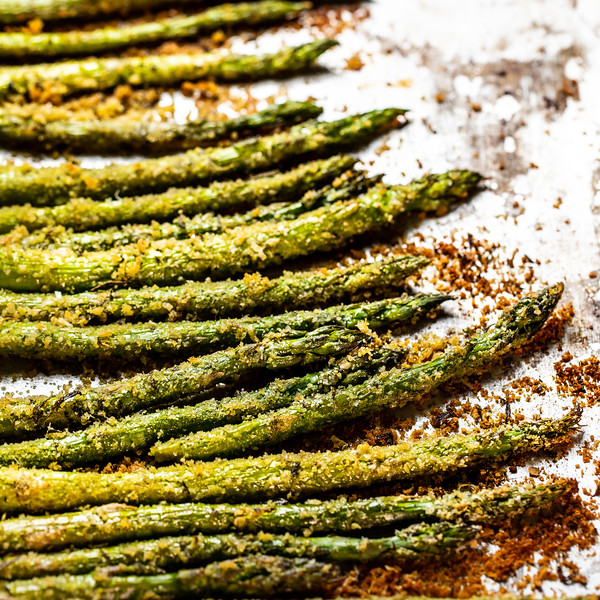 Close up of crispy roasted asparagus on a baking sheet.