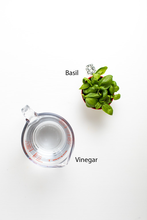 Basil and a measuring cup with vinegar.