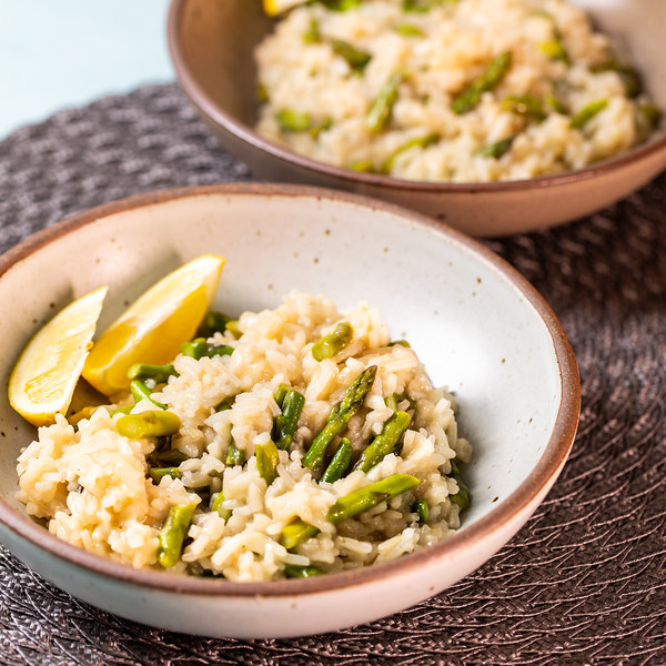 Two bowls of asparagus risotto with lemon wedges.