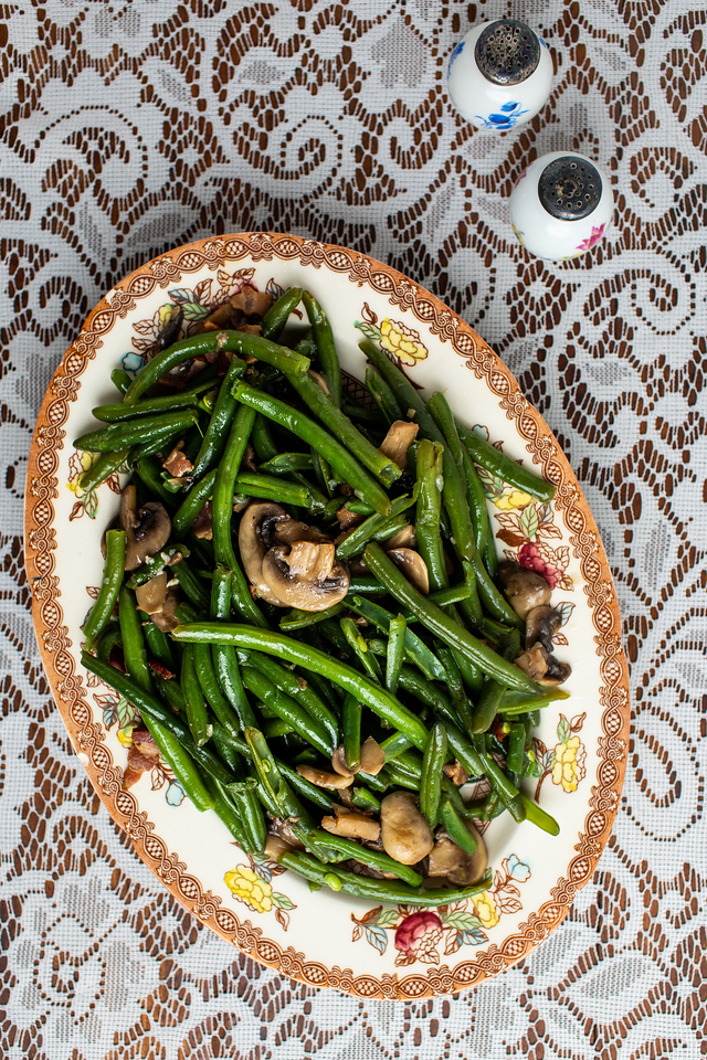 Platter of green beans with mushrooms and bacon on a lace tablecloth.