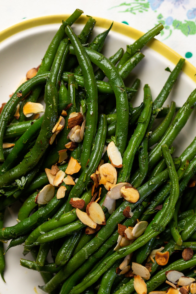 Green beans covered with toasted almonds on a platter.