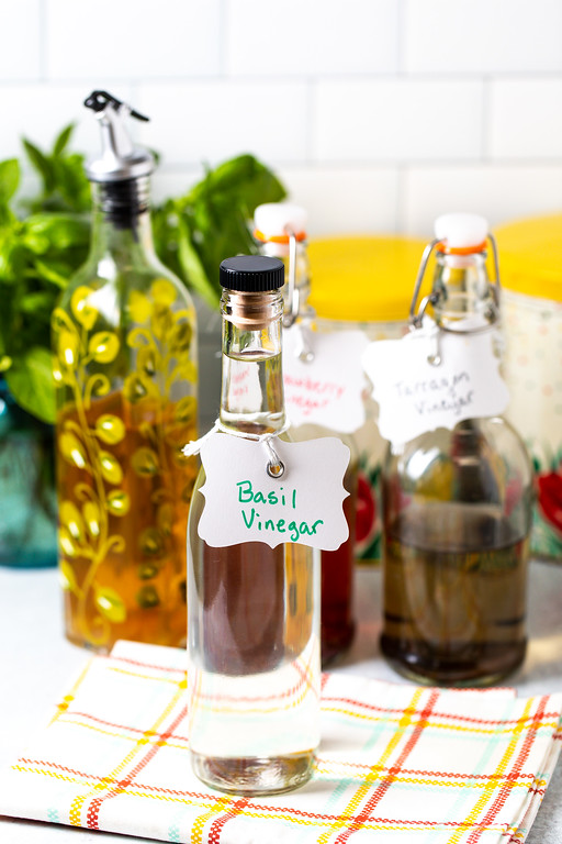 Bottle of basil vinegar with other herbed vinegars behind it.