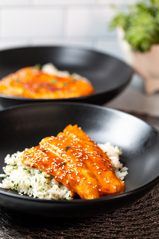 Glazed salmon over rice in a black bowl.