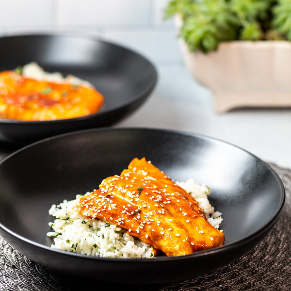 Black bowl with glazed salmon over rice.
