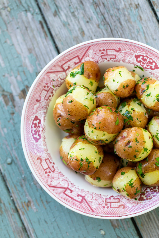 Potatoes with parsley in a vintage red and white bowl on a chippy paint blue table.