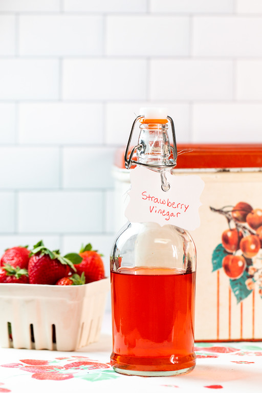 Bottle of red liquid with a label reading strawberry vinegar.