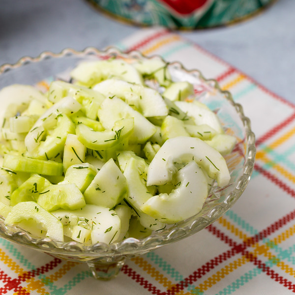 Bowl of cucumber salad on a dish towel.