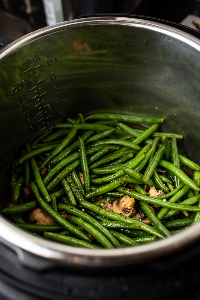Cooked green beans with mushrooms and bacon in an Instant Pot.