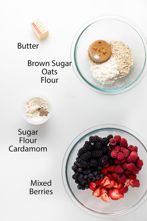 Butter, brown sugar, oats, flour, sugar, flour, cardamom, and mixed berries in a bowl.