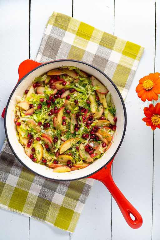 Red and white skillet with cabbage, apples, pomegranate seeds and fresh dill.