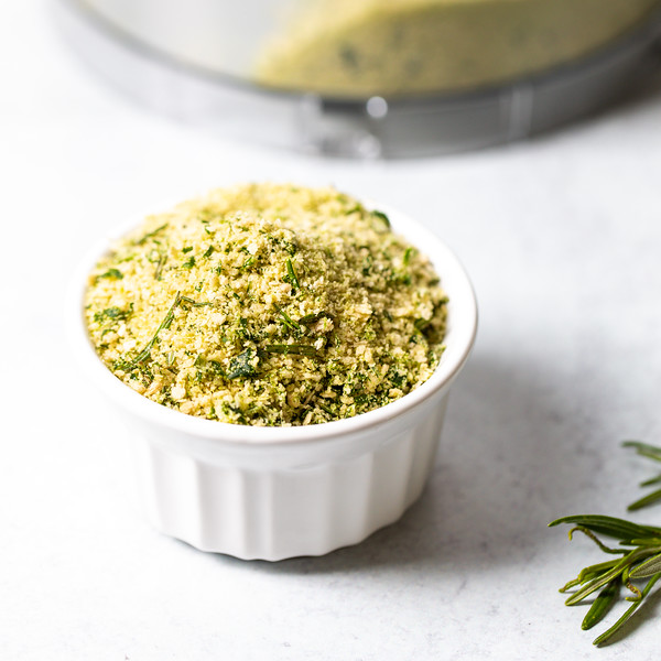 White bowl with herb flecked bread crumbs.
