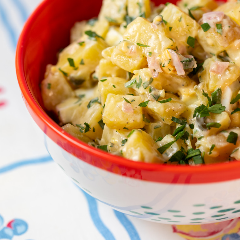Close up of potato salad in a red bowl.