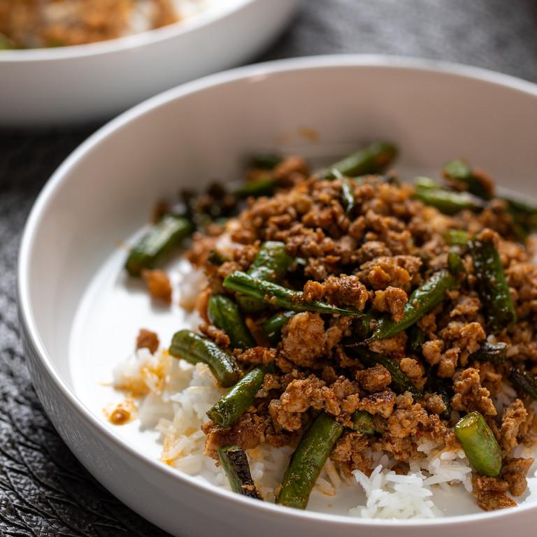 Pork and green bean stir fry over rice.