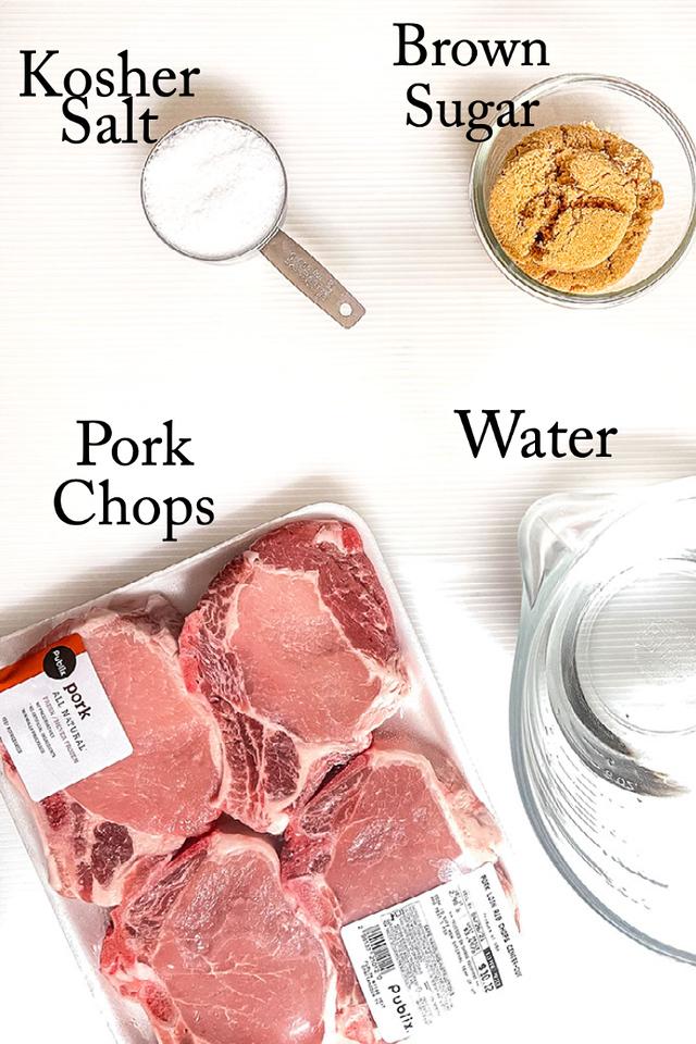 Kosher salt, sugar, pork chops and water on a white background.