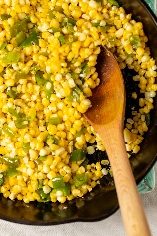 Corn and green peppers in a cast iron skillet with a wooden spoon.